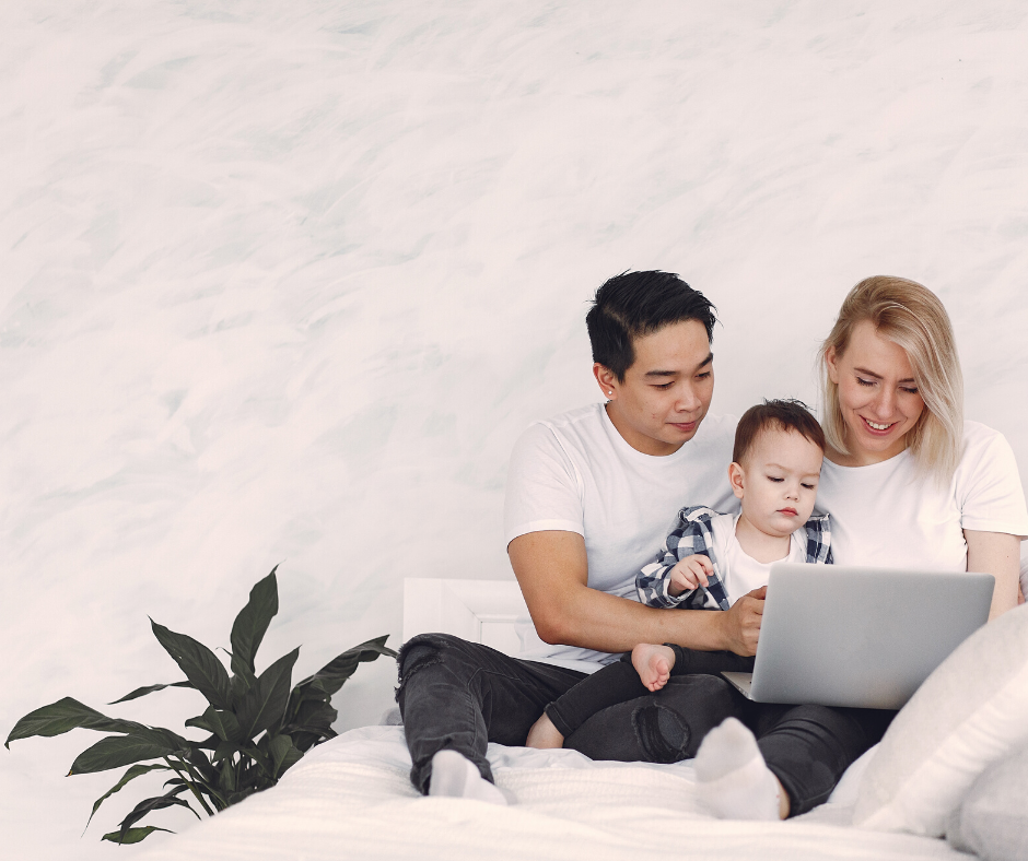 picture of 2 adults with baby viewing computer